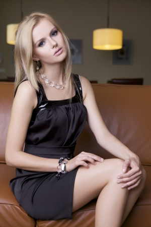 dress shoe: attractive blond woman in black dress sitting on the couch