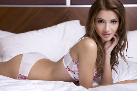 Beautiful young blonde woman in lingerie lying on the bed Stock Photo - 10717747