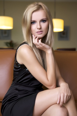 attractive blond woman in black dress sitting on the couch photo