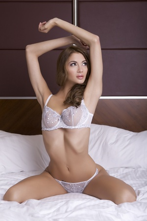 Beautiful young blonde woman in lingerie lying on the bed Stock Photo - 10869133