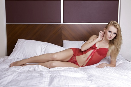 Young sexy blond woman in sexy red lingerie lying on the bed Stock Photo - 11144757