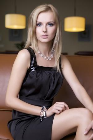 mujer sentada: atractiva mujer rubia en traje negro sentado en el sofá