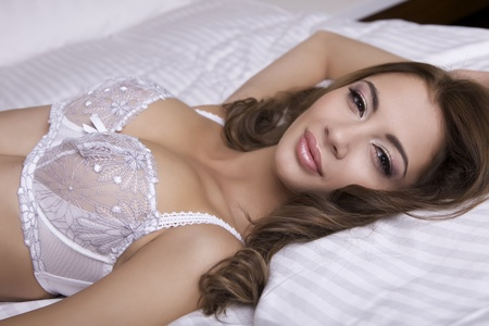 Beautiful young blonde woman in lingerie lying on the bed Stock Photo - 11145810