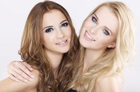 Two smiling attractive girl friends - blond and brunette on white background