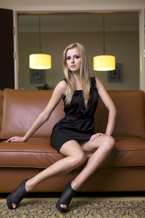 babe: attractive blond woman in black dress sitting on the couch