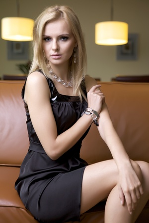 high fashion model: attractive blond woman in black dress sitting on the couch