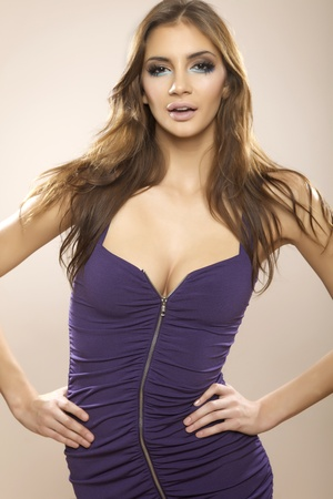Sexy brunette woman posing in violet dress. photo