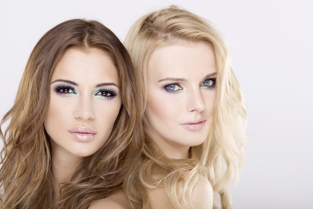 Two attractive girl friends - blond and brunette on white background Stock Photo