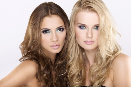 Two attractive girl friends - blond and brunette on white background photo