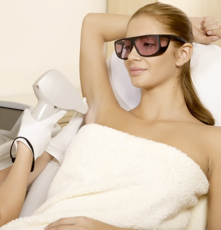 Young brunette woman receiving laser therapy. Spa studio shot photo
