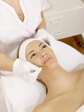 tratamiento facial: Mujer joven morena de recibir la terapia con l�ser. Spa foto de estudio