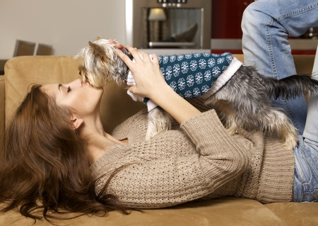 Cute young brunette girl with her Yorkshire terrier puppy lying on sofa photo