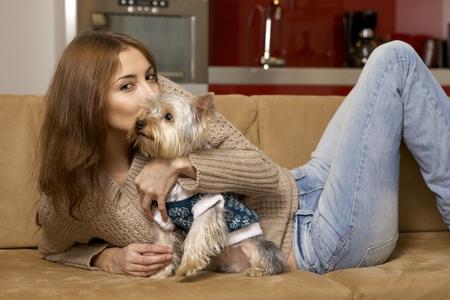 Cute jeune fille brune avec son chiot Yorkshire terrier couch� sur le canap� photo