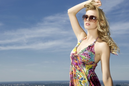 portrait of beautiful blonde girl in sunglasses on background blue sky Stock Photo