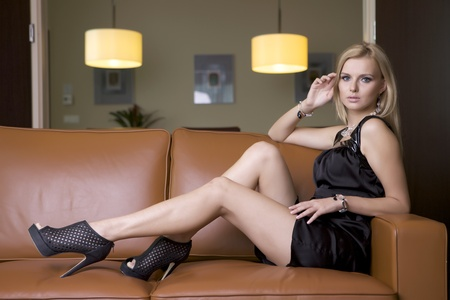 attractive femme blonde en robe noire assise sur le canap� photo