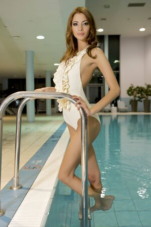 Portrait of a beautiful and attractive young woman standing in a swimming pool.