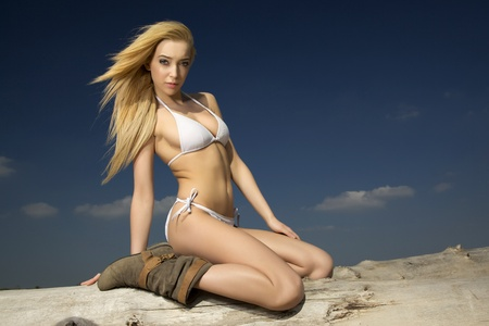 beautiful blonde woman in white bikini posing on a log photo