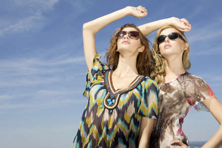 two beautiful brunette and blonde girl in sunglasses on background blue sky photo
