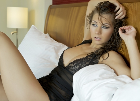 Beautiful and sexy brunette young woman wearing black lingerie in bed photo
