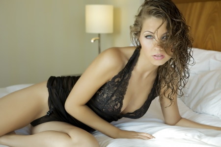 Beautiful and sexy brunette young woman wearing black lingerie in bed