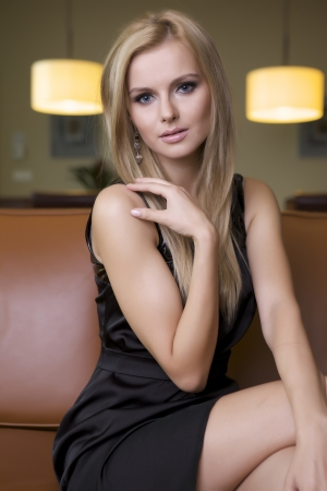 blond brown: attractive blond woman in black dress sitting on the couch