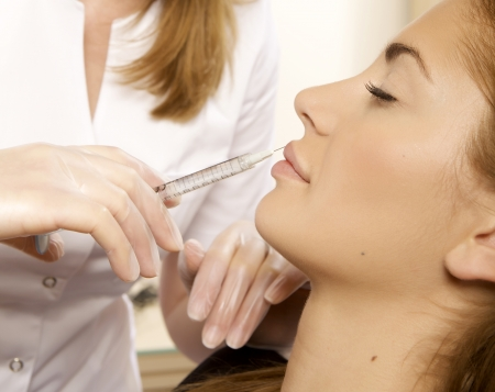 young beautiful woman having an injection mesotherapy photo