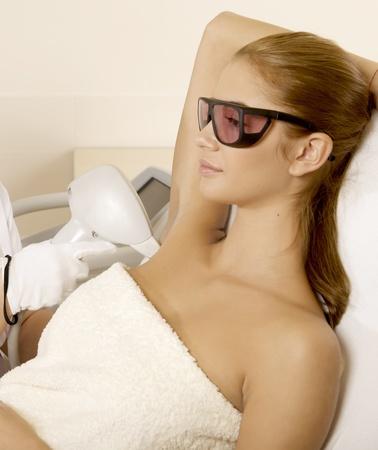 tratamientos corporales: Mujer joven morena recibiendo terapia con l�ser. Spa disparo de estudio