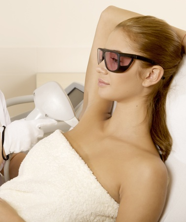 lasers: Young brunette woman receiving laser therapy. Spa studio shot