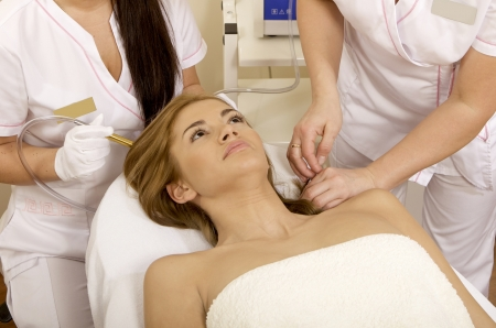Young brunette woman receiving laser therapy. Spa studio shot Stock Photo - 14051215