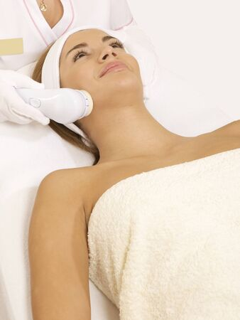 Young brunette woman receiving laser therapy. Spa studio shot Stock Photo - 14051231