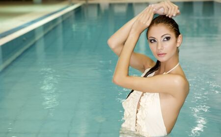 Portrait of a beautiful and attractive young woman standing in a swimming pool.  photo