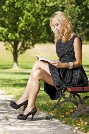 Young attracive blone woman reading book in park outdoor photo