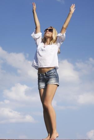 portrait of beautiful blonde girl in sunglasses on background blue sky Standard-Bild