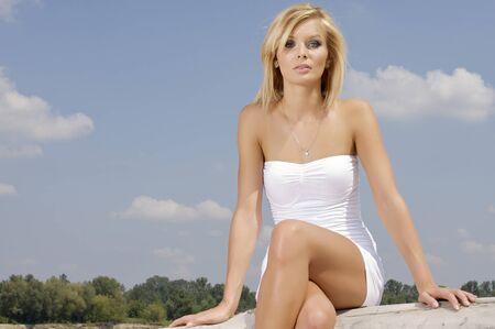 portrait of beautiful blonde girl on background blue sky