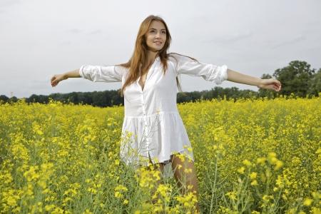 Beautiful and sensuality brunette woman in a yellow flowers field Reklamní fotografie