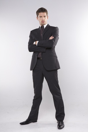 fashion shot of an elegant young man wearing suit on grey background photo