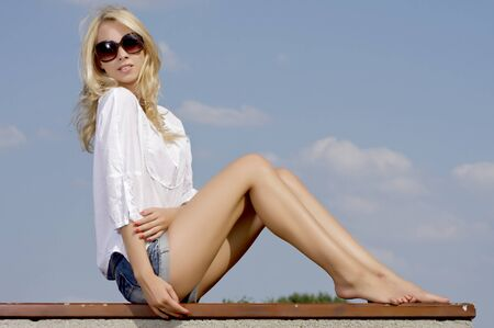 portrait of beautiful blonde girl in sunglasses on background blue sky photo