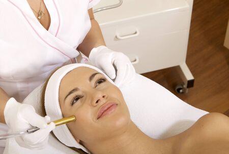 gezichtsbehandeling: Jonge brunette vrouw die lasertherapie. Spa studio shot