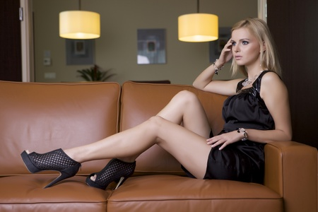 jolie femme blonde en robe noire assise sur le canap� photo
