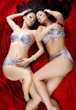two sexy beautiful brunette girls lying on red background bright diamond makeup long corly hair silver diamond lingerie photo