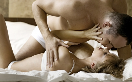 intimate young couple during foreplay in bed photo