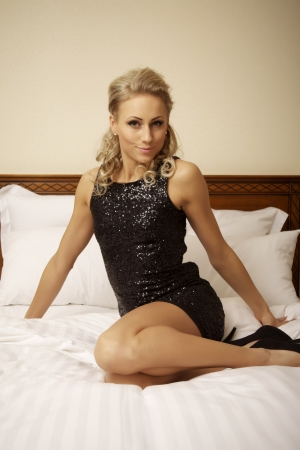 attractive blond woman in elegant fashiontable black dress lie on the bed photo