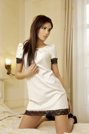 Beautiful and attractive female brunette woman posing in white dress on bed Stock Photo - 18032796