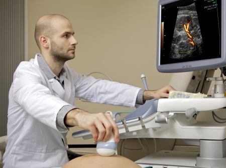 sonography: Portrait of young male technician operating ultrasound machine in white dress