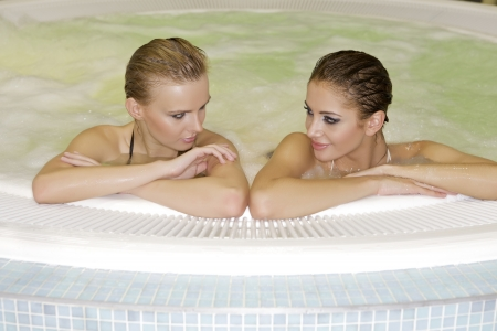 two young beautiful brunette girls in jacuzzi photo