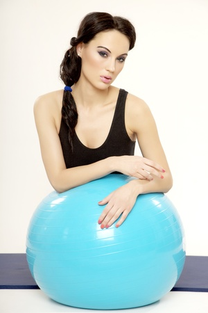 Attractive young brunette sporty woman in black dress with blue fitness ball isolated on white background