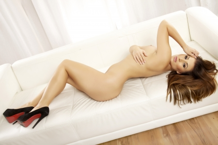 Sexy  woman naked: portrait of a beautiful young adult sensuality brunette naked woman in white sofa
