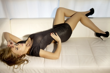 Beautiful and attractive female blonde woman posing in silver black dress on bed photo
