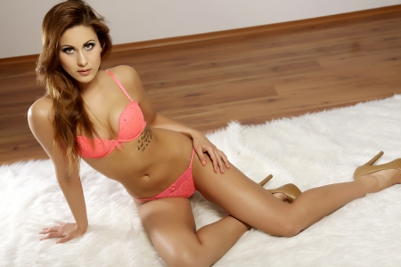 Beautiful and sexy young attractive woman wearing pink lingerie in bed on white carpet photo