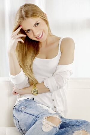 Beautiful and attractive young adult smile blonde woman posing in blue jeans and white shirt sweater on the white sofa photo